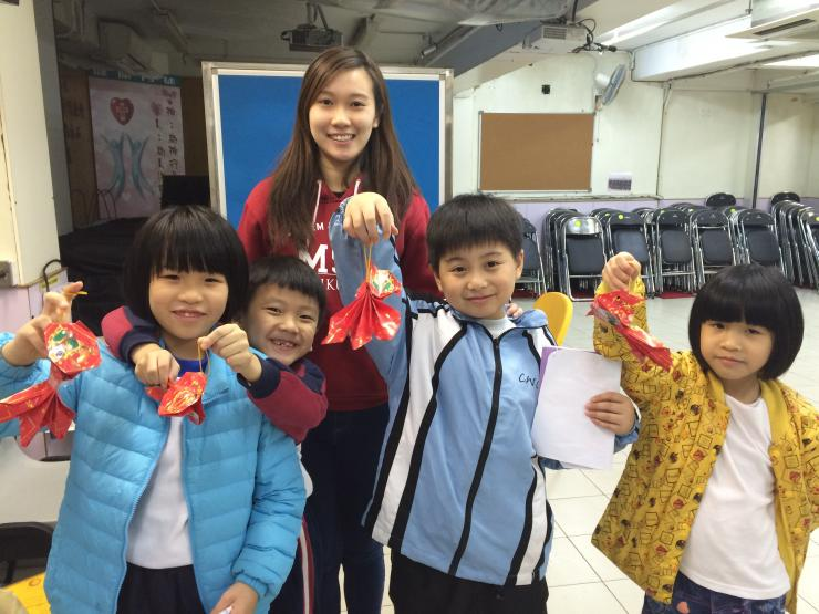 Student leaders and children smiling happily with the Chinese New Year crafts in hand